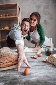 Giovane e donna che provano a prendere l'uovo