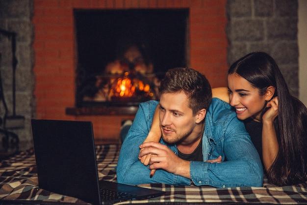 Giovane e donna che si trovano insieme sulla coperta sul pavimento. guardano film sul portatile. la coppia è felice sono vicino al camino.