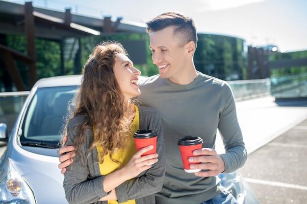 Giovane e donna con caffè vicino ad un'automobile