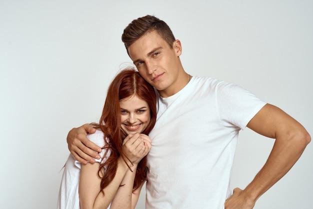 Giovane e donna in magliette bianche su una luce