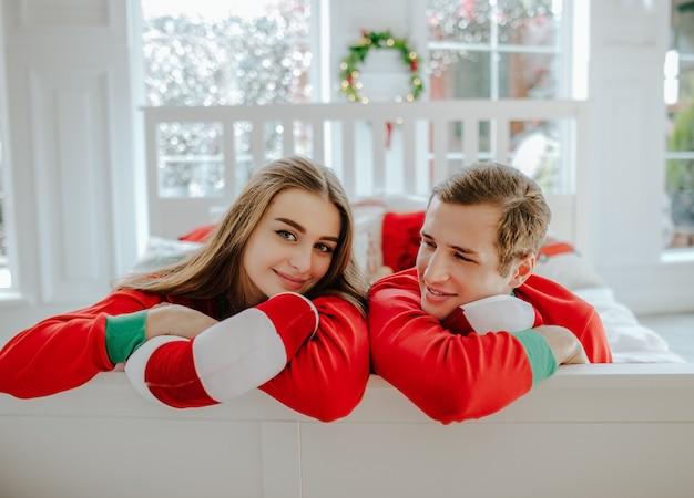 Giovane e donna in pigiama di natale rosso posa su un letto bianco nella stanza della stanza con una grande finestra.