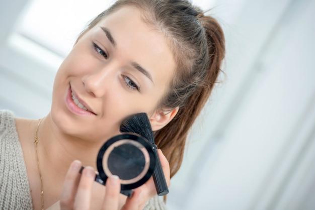 Giovane e donna sorridente che applica polvere sul suo fronte