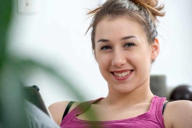 Giovane e donna sorridente che per mezzo dello smartphone a casa