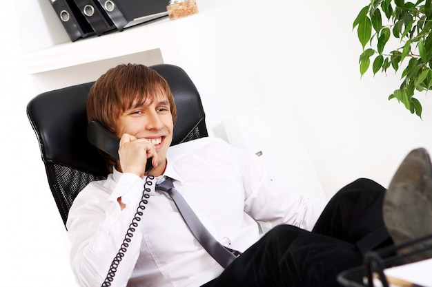 Giovane e imprenditore di successo che parla al telefono