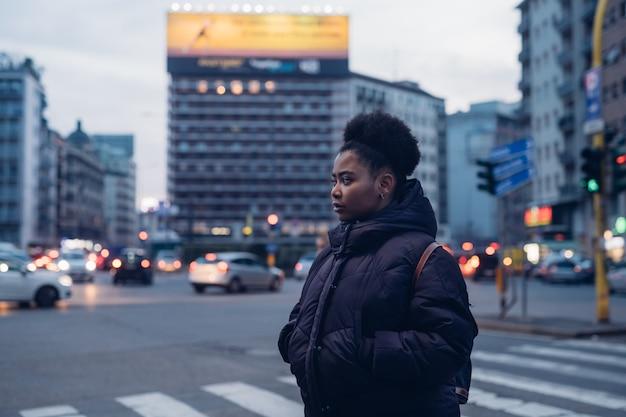 Giovane e riccia ragazza nera in strada