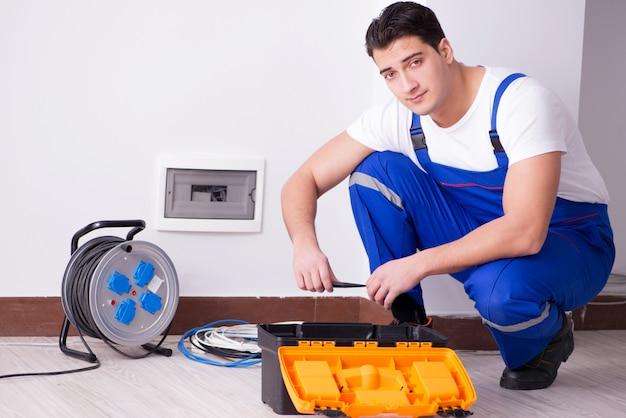 Giovane elettricista che lavora allo zoccolo a casa