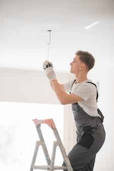 Giovane elettricista sorridente con un cacciavite che ripara una lampada da soffitto all'interno. spazio per il testo