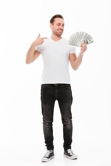 Giovane emozionante che indica e che tiene soldi.