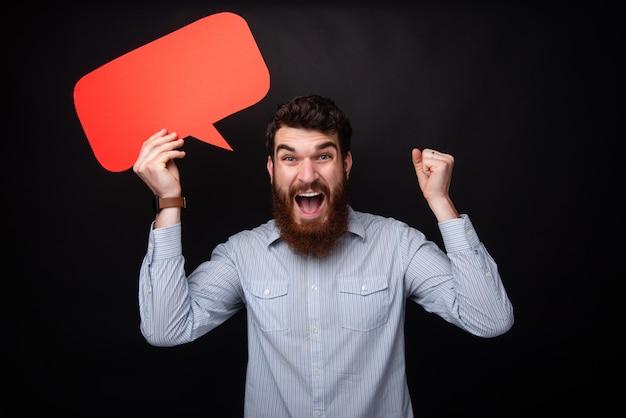 Giovane emozionante con la barba che grida e che tiene rosso un discorso della bolla, sopra fondo isolato grigio scuro
