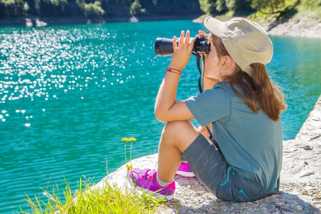 Giovane escursionista guarda il panorama con il telescopio