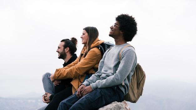 Giovane escursionista maschio e femmina felice che si siede sulla roccia contro il cielo