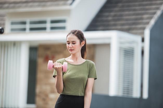 Giovane esercitazione asiatica della donna all'aperto