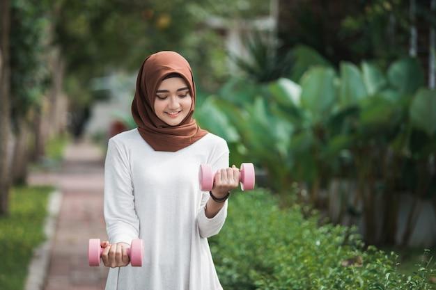Giovane esercitazione musulmana asiatica della donna all'aperto