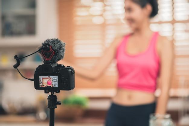 Giovane esercizio asiatico della donna di blogger e guardare alla macchina fotografica in cucina