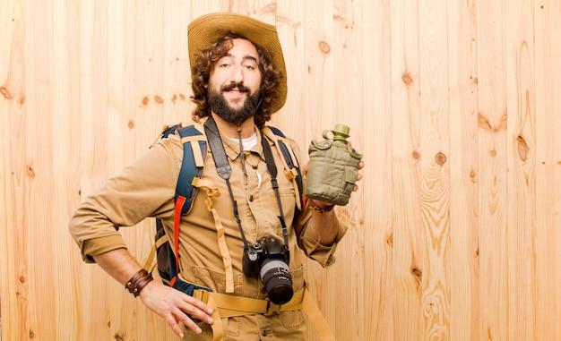 Giovane esploratore pazzo con il cappello di paglia e lo zaino su fondo di legno