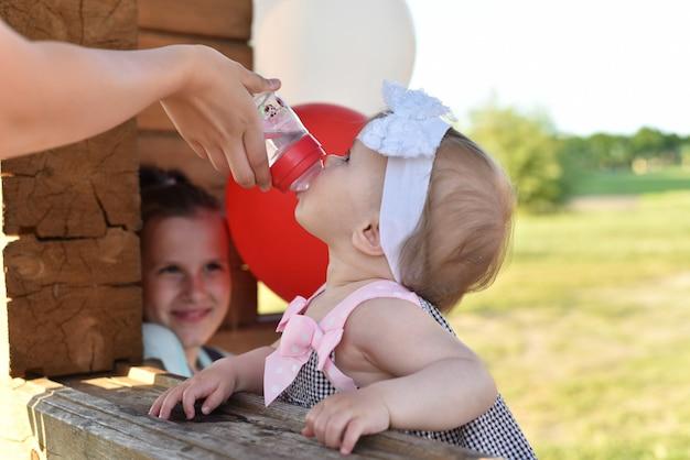 Giovane famiglia amichevole con i bambini che riposano di estate in natura