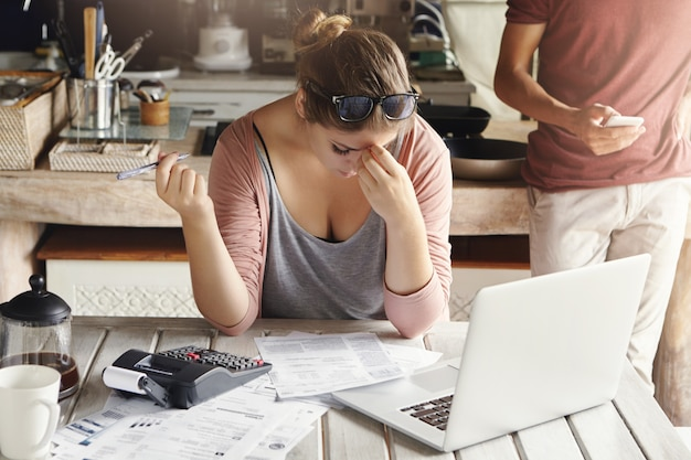 Giovane famiglia che affronta problemi di debito. donna sollecitata che tiene la sua testa nella frustrazione, facendo i conti bancari e facendo i calcoli necessari usando il computer portatile e il calcolatore