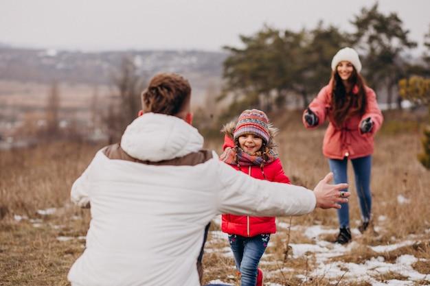 Giovane famiglia che cammina insieme nella foresta all'orario invernale