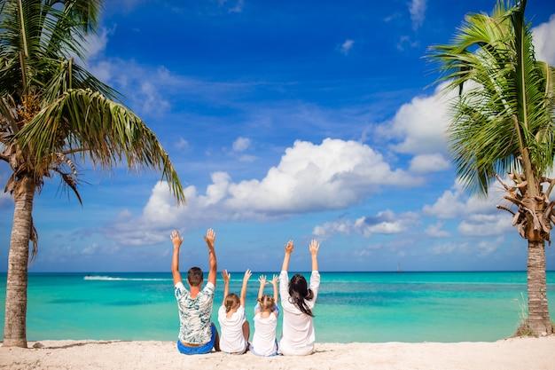 Giovane famiglia che cammina sulla spiaggia caraibica tropicale bianca
