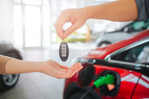 Giovane famiglia che compra prima automobile elettrica nello showroom