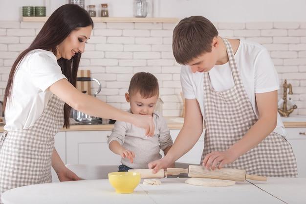 Giovane famiglia che cucina insieme. marito, moglie e il loro bambino piccolo in cucina. famiglia che impasta la pasta con farina. la gente cucina la cena o la colazione.