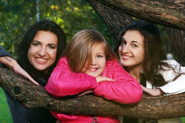 Giovane famiglia che fa passeggiata sana attraverso il parco di autunno