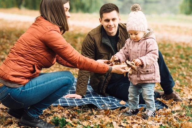 Giovane famiglia che gioca con le foglie nella foresta di autunno