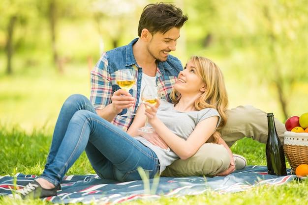 Giovane famiglia che ha picnic nel parco e che beve vino.