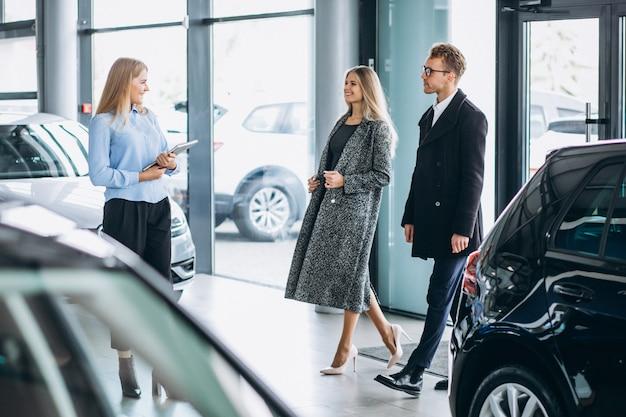 Giovane famiglia che sceglie un'automobile in una sala d'esposizione dell'automobile