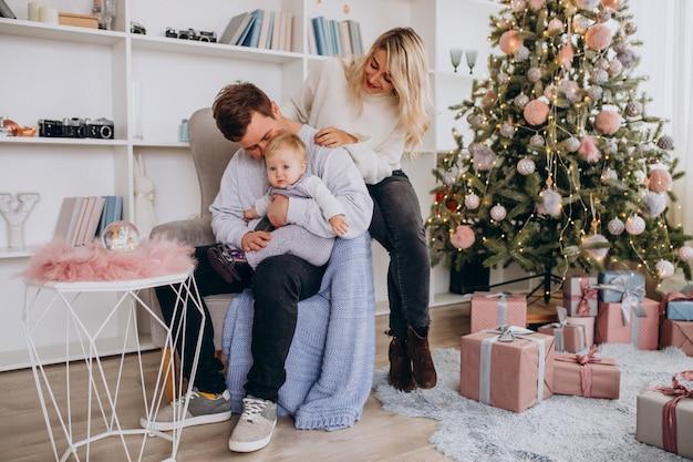 Giovane famiglia con bambina seduta da albero di natale