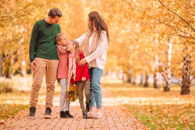 Giovane famiglia con bambini piccoli nella sosta di autunno il giorno pieno di sole. ritratto di autunno della famiglia