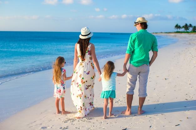 Giovane famiglia con due bambini in vacanza tropicale la sera