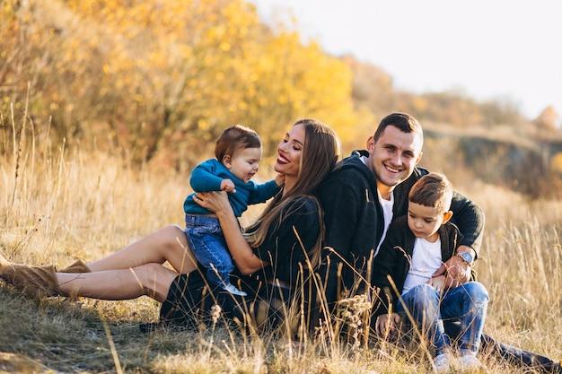 Giovane famiglia con due figli seduti insieme nel parco