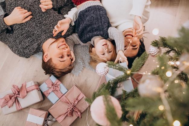 Giovane famiglia con figlio piccolo sotto l'albero di natale