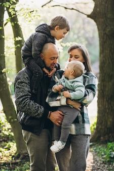 Giovane famiglia con i loro bambini che si divertono nella foresta