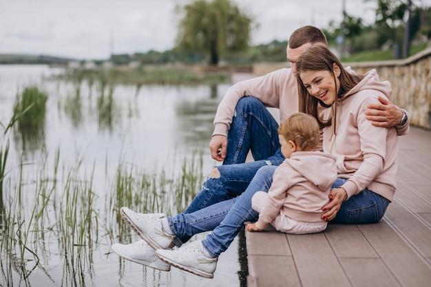 Giovane famiglia con il loro piccolo bambino nel parco in riva al lago