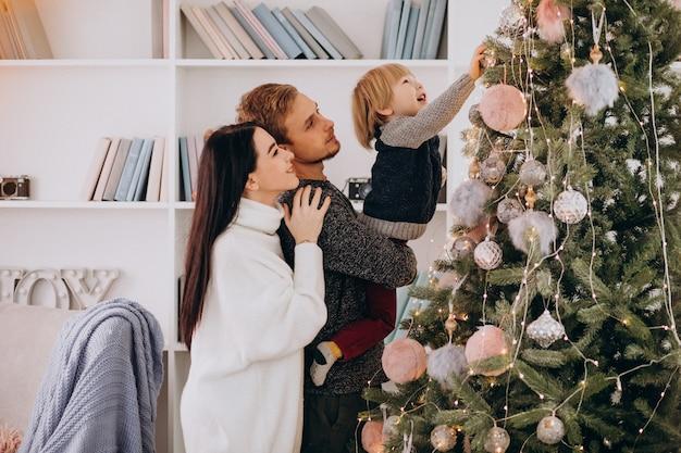 Giovane famiglia con il piccolo figlio che decora l'albero di natale