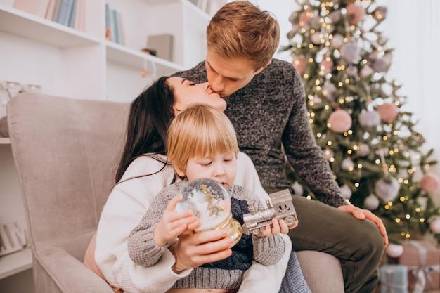 Giovane famiglia con il piccolo figlio che si siede dall'albero di natale che disimballa i regali