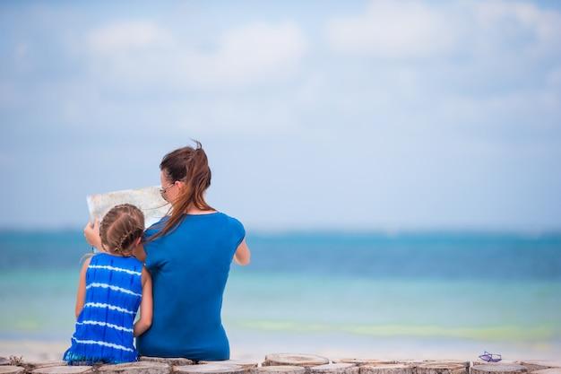 Giovane famiglia con la mappa dell'isola sulla spiaggia bianca