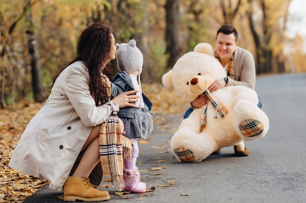 Giovane famiglia con la piccola figlia al giocattolo del grande orso del presente della strada del parco di autunno