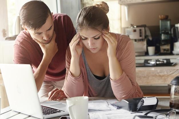 Giovane famiglia con molti debiti che affrontano lo stress finanziario