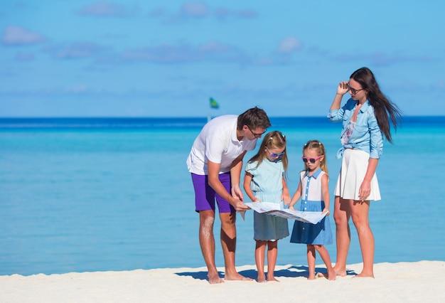 Giovane famiglia di quattro felice con la mappa sulla spiaggia