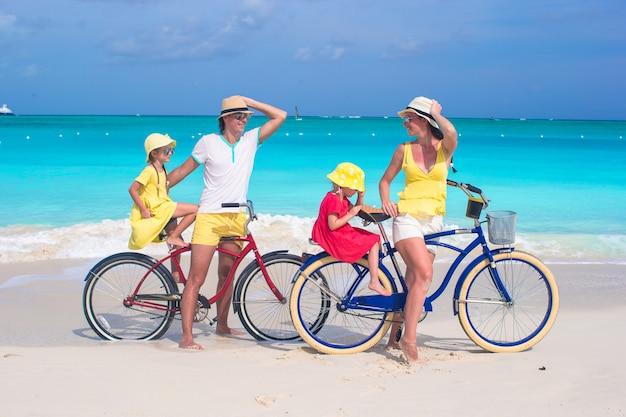 Giovane famiglia di quattro in sella a biciclette sulla spiaggia tropicale di sabbia