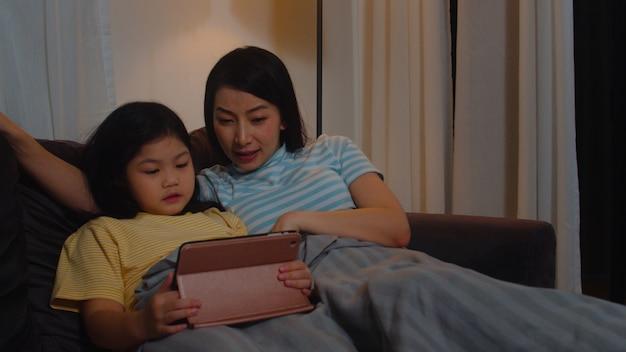 Giovane famiglia e figlia asiatiche felici facendo uso della compressa a casa. la madre coreana si rilassa con il film di sorveglianza della bambina che si trova sul sofà prima di andare a dormire in salone alla casa moderna nella notte.