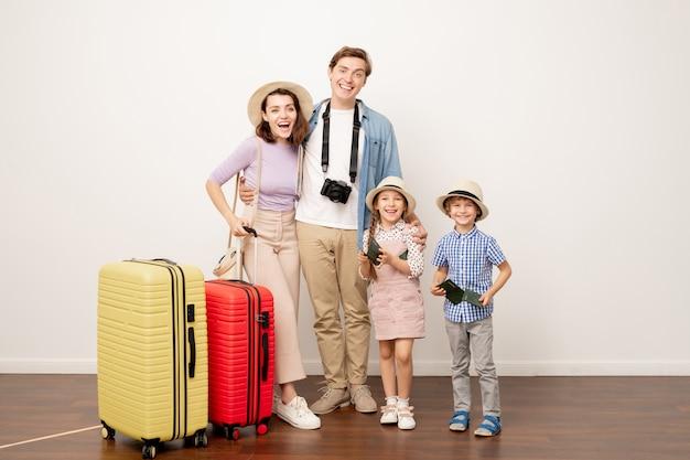 Giovane famiglia entusiasta di due genitori e i loro bambini carini in abbigliamento casual con valigie pronte per il viaggio
