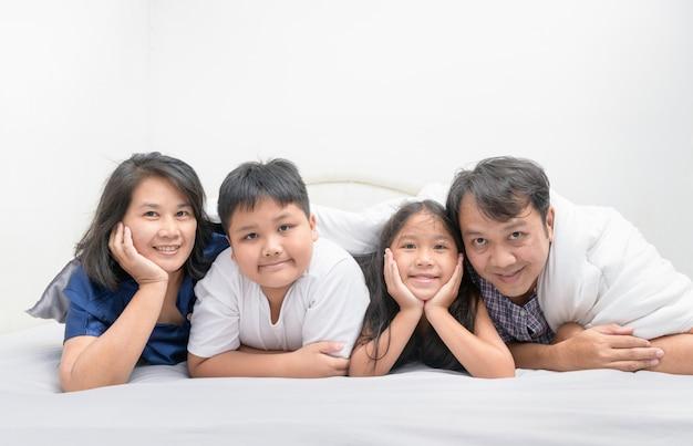 Giovane famiglia felice asiatica che si trova insieme a letto