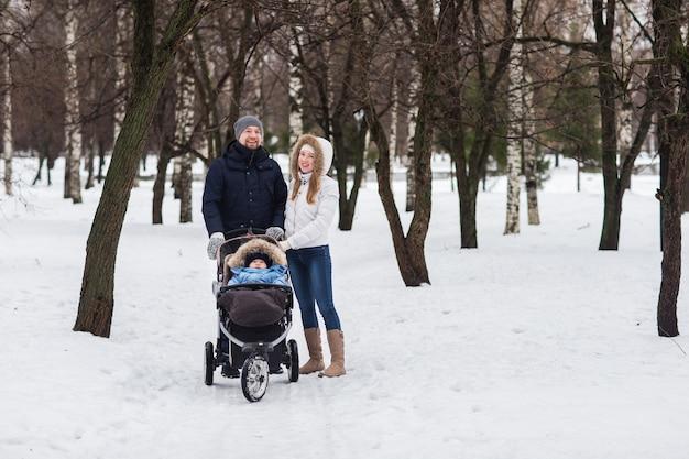 Giovane famiglia felice che cammina nel parco in inverno
