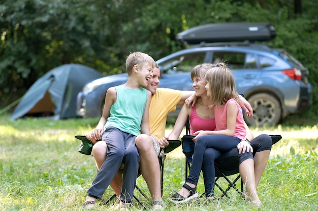 Giovane famiglia felice che gode del tempo al capmsite all'aperto. genitori e figli seduti insieme e parlano felicemente.