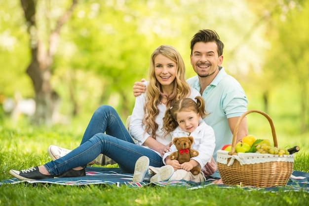 Giovane famiglia felice che ha picnic all'aperto.