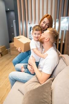 Giovane famiglia felice con il bambino che disimballa le scatole che si siedono insieme sul sofà